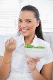 Cheerful pretty woman eating healthy salad sitting on sofa Stock Photo