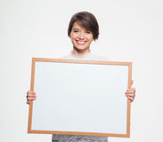 Cheerful pretty woman holding blank board in front of herself Royalty Free Stock Photos