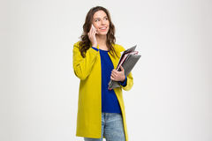 Cheerful pretty woman holding folders and talking on cellphone Royalty Free Stock Images