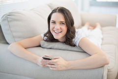 Cheerful pretty woman lying on a cosy couch sending text message Stock Photo