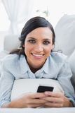 Cheerful pretty woman lying on the couch using her smartphone Royalty Free Stock Photography