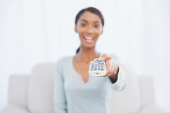 Cheerful pretty woman sitting on sofa changing tv channel Stock Photography
