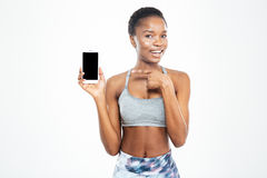 Cheerful pretty young african american sportswoman holding blank screen smartphone Stock Photo
