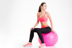 Cheerful pretty young fitness woman sitting on pink fitball Stock Photos