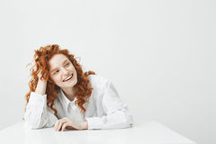 Cheerful pretty young girl with foxy hair smiling laughing sitting at table over white background. Copy space Stock Images