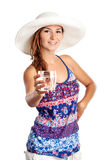 Cheerful pretty young girl with a glass of water. Cheerful pretty young girl in summerwear holding a glass of water, against white background Stock Photo