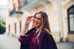 Cheerful pretty young lady holds his glasses her hands and smiles at his interlocutor. Girl wearing stylish burgundy coat and a shirt in a cage Royalty Free Stock Photo