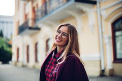 Cheerful pretty young lady holds his glasses her hands and smiles at his interlocutor.Girl wearing stylish burgundy coat and a shi. Cheerful pretty young lady Royalty Free Stock Photos