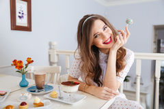 Cheerful pretty young woman eating lollipop in cafe Stock Photo