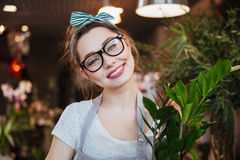 Cheerful pretty young woman florist in glasses at flower shop Royalty Free Stock Image