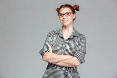 Cheerful pretty young woman in glasses standing with arms crossed Royalty Free Stock Photo