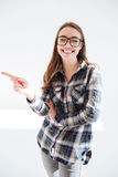 Cheerful pretty young woman in glasses standing and pointing away Royalty Free Stock Photos