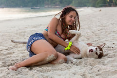 Cheerful pretty young woman in hat sitting and hugging her dog on the beach Royalty Free Stock Photos