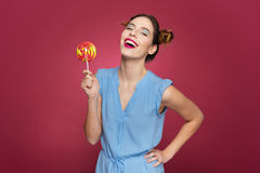 Cheerful pretty young woman holding colorful lollipop and laughing Stock Photography