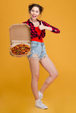 Cheerful pretty young woman holding pizza and showing thumbs up Royalty Free Stock Photography