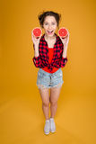 Cheerful Pretty Young Woman Holding Two Halves Of Grapefruit Royalty Free Stock Photo