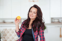 Cheerful pretty young woman showing half of orange sitting on the kitchen stock photography
