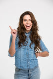 Cheerful pretty young woman standing and pointing away Royalty Free Stock Image
