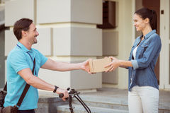Cheerful professional courier delivering parcel to the client Royalty Free Stock Photos