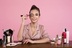 Cheerful professional makeup artist is expressing gladness. Portrait of optimistic young female cosmetologist is sitting at dressing table with cosmetics items royalty free stock images