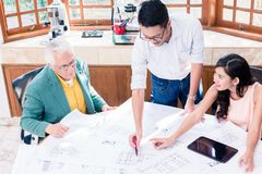 Cheerful professional team working on an innovative project. Cheerful professional team looking at camera while working together on an innovative project stock photos