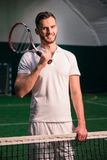 Cheerful professional tennis player holding racket. Set goals. Positive handsome professional tennis player standing near net and holding racket on the shoulder Royalty Free Stock Photos