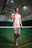 Cheerful professional tennis player training in indoor court. Switch on positivity. Low angle of delighted positive hadsome tennis player holding racket on the Stock Photo