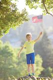 Boy celebrating independence day. Cheerful proud little boy holding american flag celebrating 4th of july, independence day, or memorial day Royalty Free Stock Photography