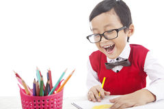 Cheerful pupil drawing with crayons Royalty Free Stock Image