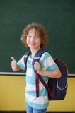 The cheerful pupil stands near a board in class. Royalty Free Stock Photo