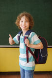 The cheerful pupil stands near a board in class. Stock Image