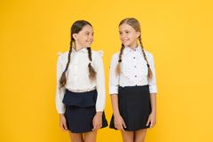 Cheerful pupils. little girls on yellow background. friendship and sisterhood. best friends. kid formal fashion. Education abroad. smart looking children stock photography