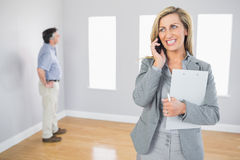 Cheerful realtor calling someone with her mobile phone. With potential buyer in background Royalty Free Stock Photography