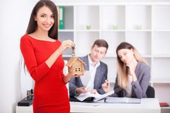 Cheerful realtor giving house key to happy property owners, youn. G men taking keys to rented or purchased home, making deal with real estate agent, couple just Royalty Free Stock Image