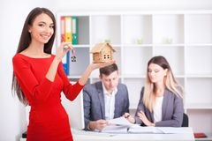 Cheerful realtor giving house key to happy property owners, youn. G men taking keys to rented or purchased home, making deal with real estate agent, couple just Stock Photography