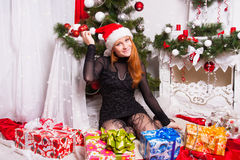 Cheerful red-haired girl in the Santa Claus hat Stock Image
