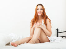 Cheerful red-haired girl in shirt sitting on white sheet in bed Stock Images