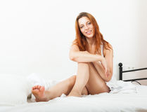 Cheerful red-haired woman awaking on white sheet in her bed at h Royalty Free Stock Photo