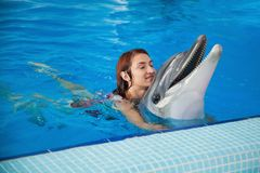 Woman and dolphin. A cheerful red-haired woman in a red bathing suit laughs, bathes and holds a dolphin in the blue pool behind her back Royalty Free Stock Photography