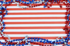 Cheerful red and white horizontal stripes form the background. Border is formed of shiny beads in red, silver and blue. Copy space. Good for USA patriotic royalty free stock image