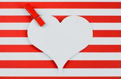 Cheerful red and white horizontal stripes form the background. A red clothespin is at the corner of a white, heart-shaped cutout. stock photo