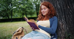 Cheerful redhead girl reading book outdoors in park smiling relaxing on grass. Cheerful redhead girl reading book outdoors in park smiling relaxing sitting on stock video footage