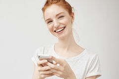 Cheerful redhead girl smiling  holding phone. Cheerful redhead girl smiling  holding phone looking at camera. Copy space. Isolated on white background Stock Image