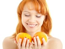 Cheerful redhead holding two oranges over white Royalty Free Stock Photos