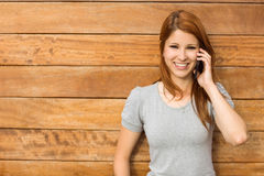 Cheerful redhead leaning against wall phoning Royalty Free Stock Photo