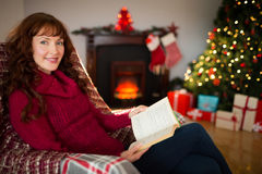 Cheerful redhead reading on the armchair at christmas Royalty Free Stock Photos