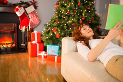 Cheerful redhead reading on the couch at christmas Stock Image