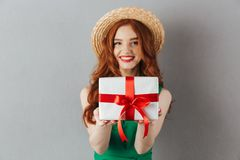 Cheerful redhead young woman in green dress holding gift. Photo of cheerful redhead young woman in green dress standing over grey wall background. Looking camera stock photo