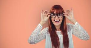Cheerful redheaded female hipster wearing eyeglasses against orange background Royalty Free Stock Photos