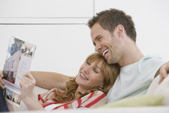 Cheerful And Relaxed Couple Reading Brochure On Sofa. Side view of a cheerful and relaxed young couple reading brochure on sofa Stock Images